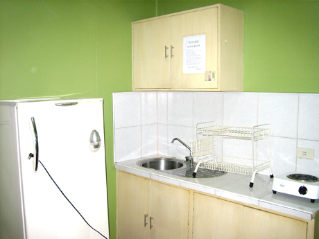 The studio-unit is complete with refrigerator, cupboard, stove and kitchen sink.